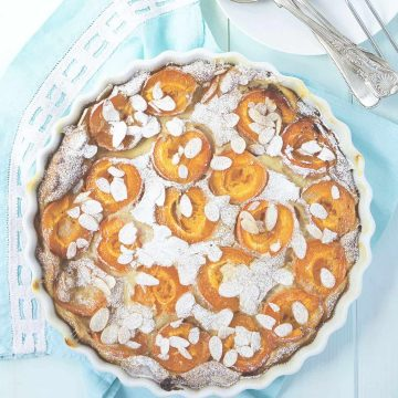 A round apricot clafoutis over a light blue background.