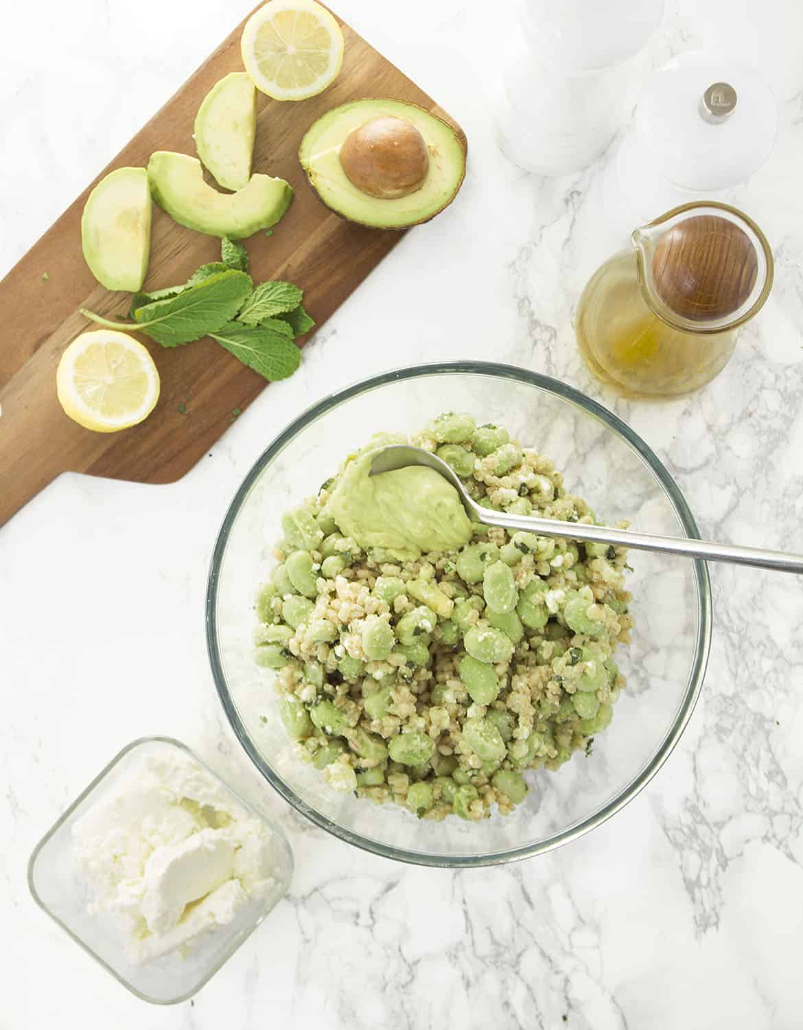 Fava bean salad on a glass bowl with a spoon fulled of avocado dressing. Oil, feta and a chopping board on the background.
