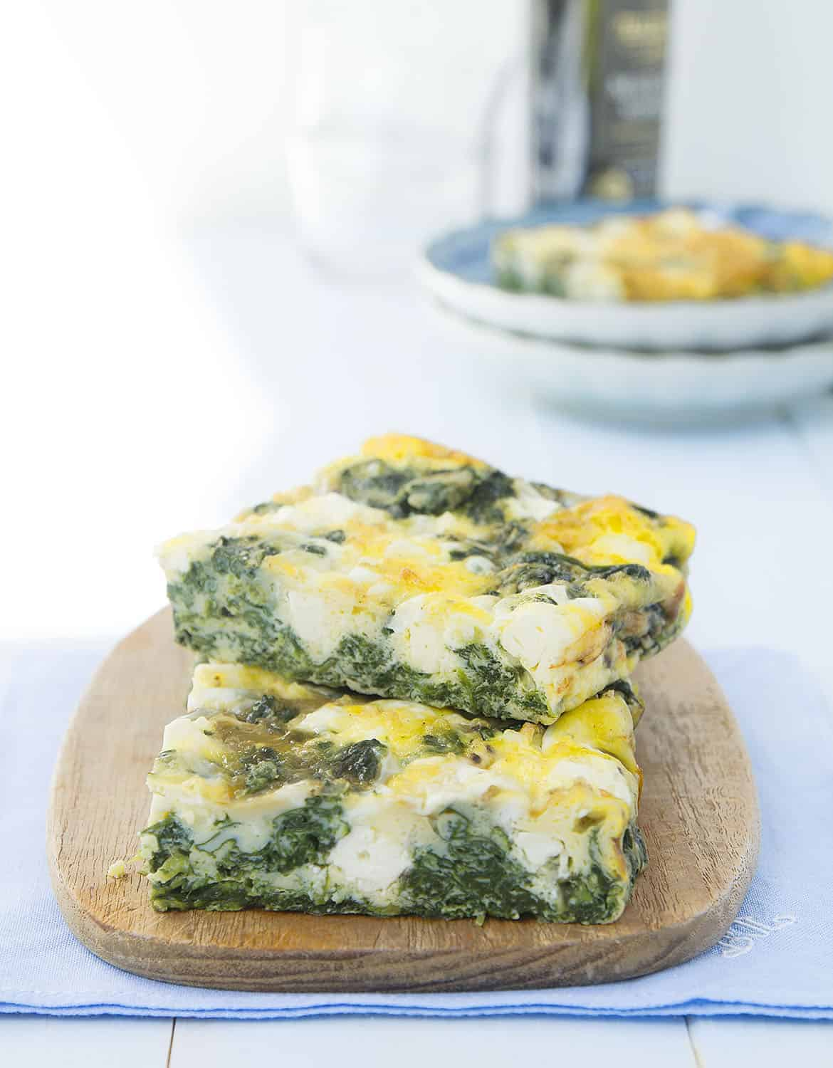 Two large slices of baked frittata with spinach and feta on a small wooden board.