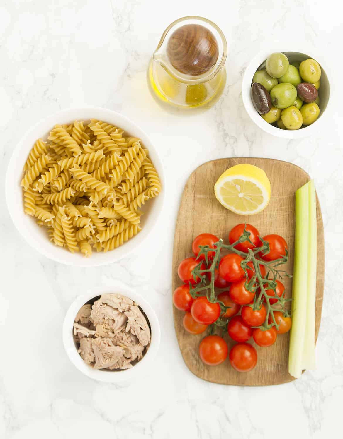 The ingredients for this tuna pasta salad are arranged on a white marble table and a wooden chopping board.