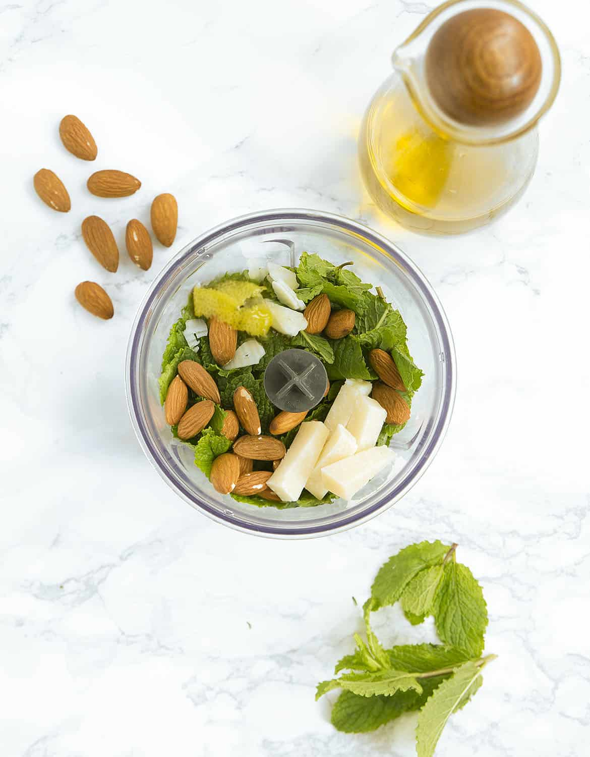 A small food processor bowl full with the ingredients to make this mint pesto.