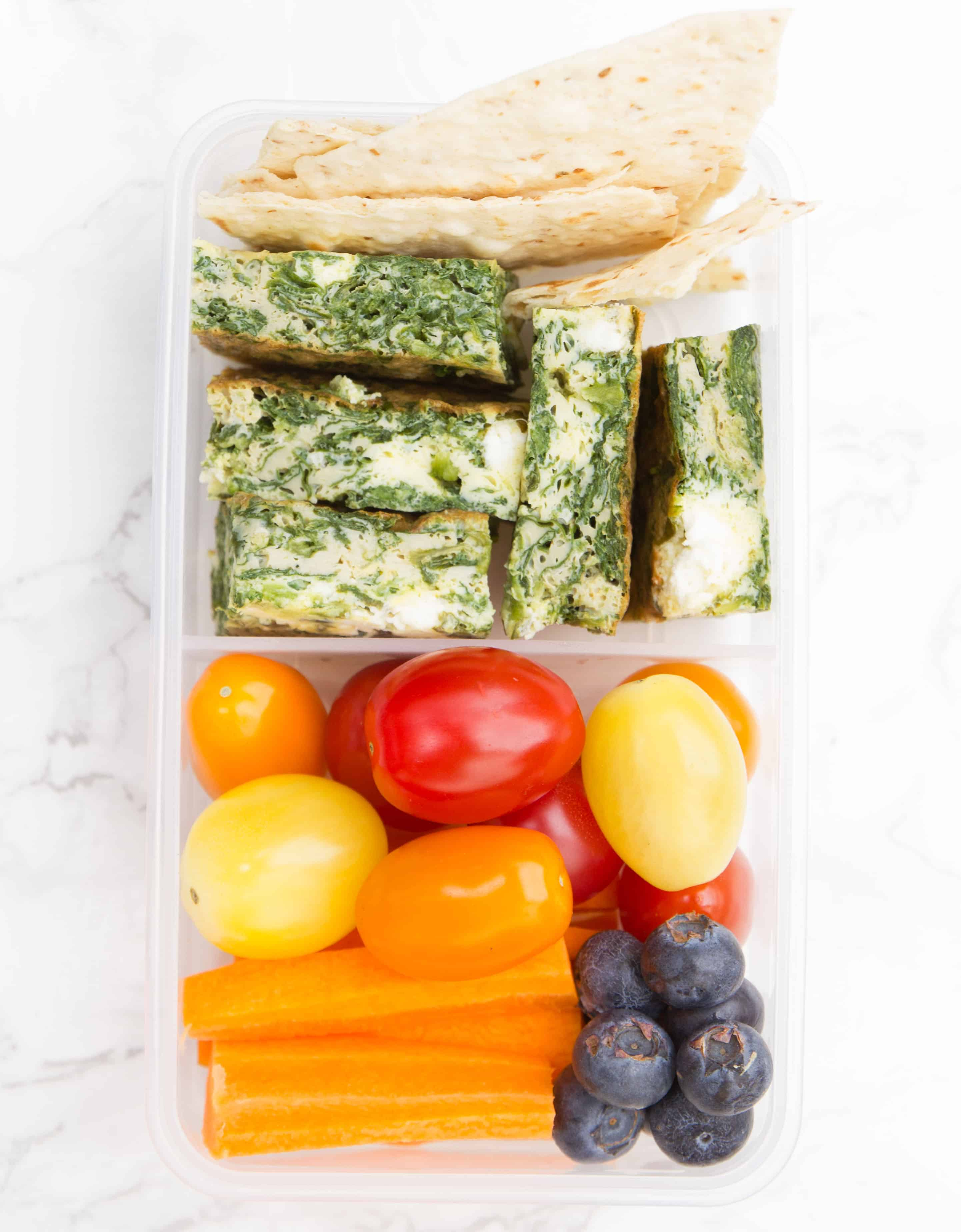 Cubes of baked frittata in a rectangular meal prep container with vegetables and blueberries.