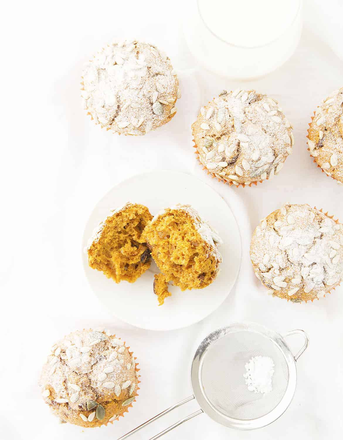 Top view of pumpkin muffins dusted with icing sugar over a white background.
