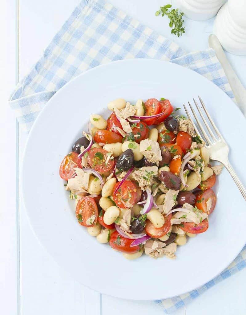 Bean, tomato and tuna salad on a light blue plate.