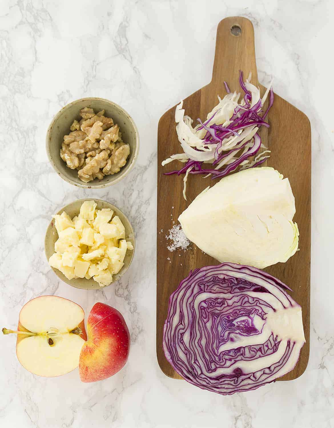 The ingredients for this cabbage salad are arranged over a chopping board and a white table.