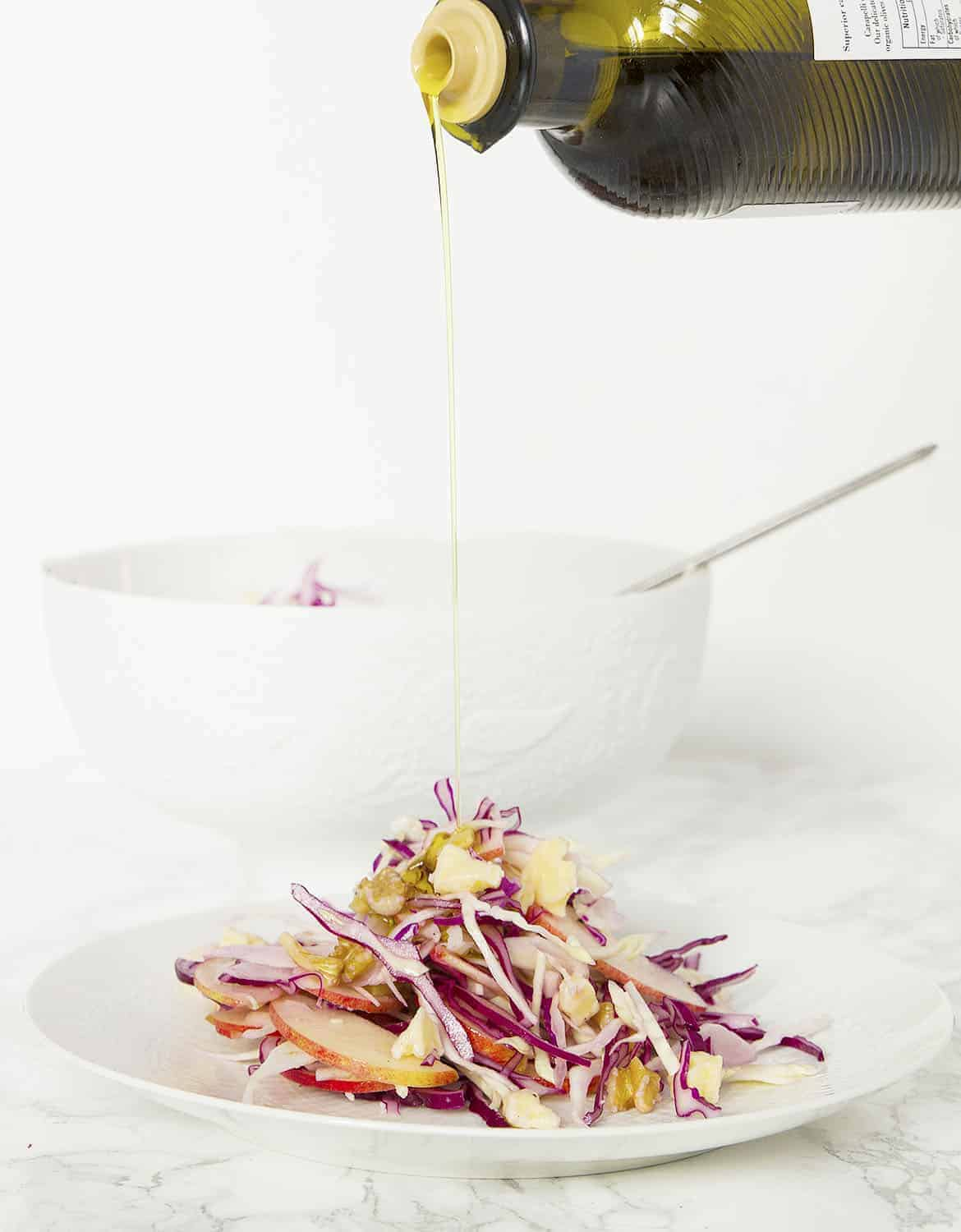A bottle pouring olive oil over a serving of cabbage salad over a white background.