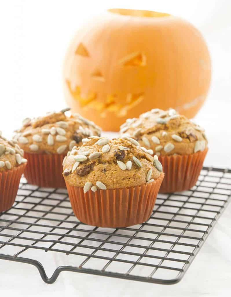 Blender pumpkin muffins on a cooling rack, a carved pumpkin in the background.