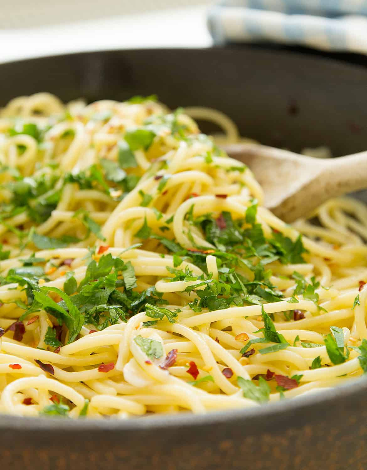 A wooden spoon is stirring spaghetti aglio e olio in a cast iron skillet.