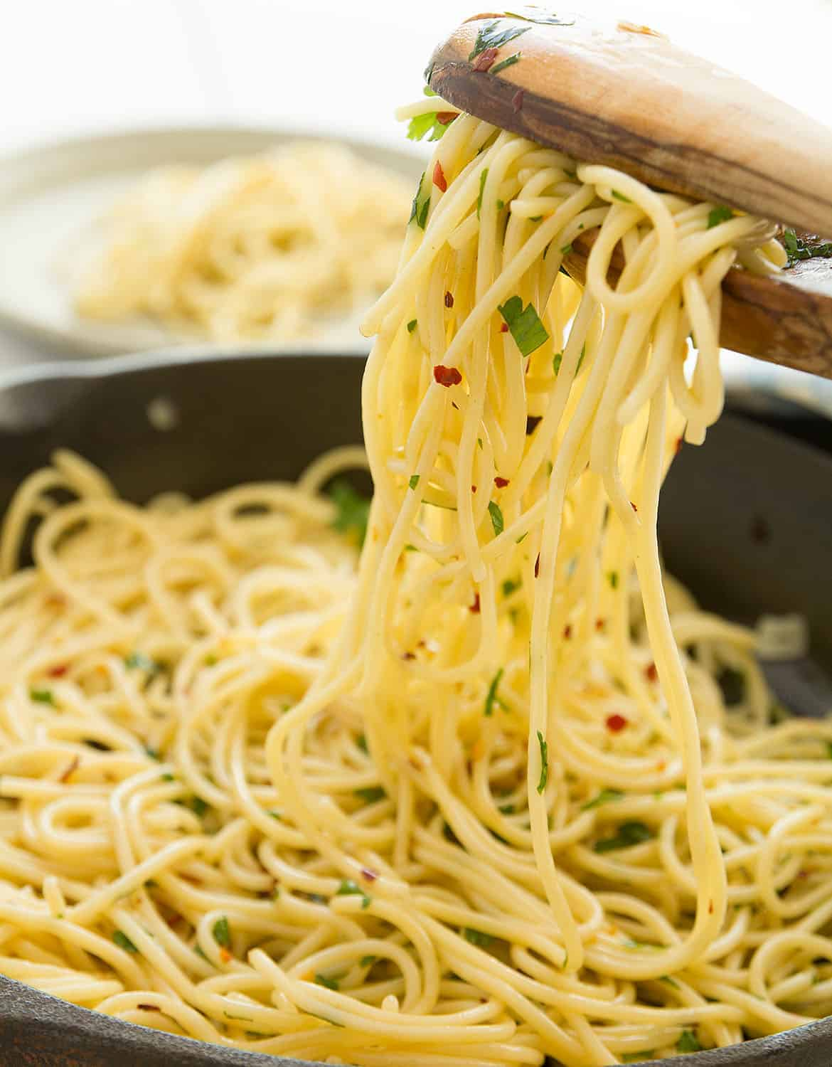 Two wooden spoons are lifting some pasta with garlic and olive oil.