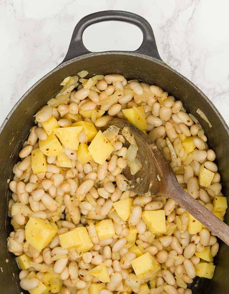 A wooden spoon is stirring white beans and potatoes inside a black cast iron.
