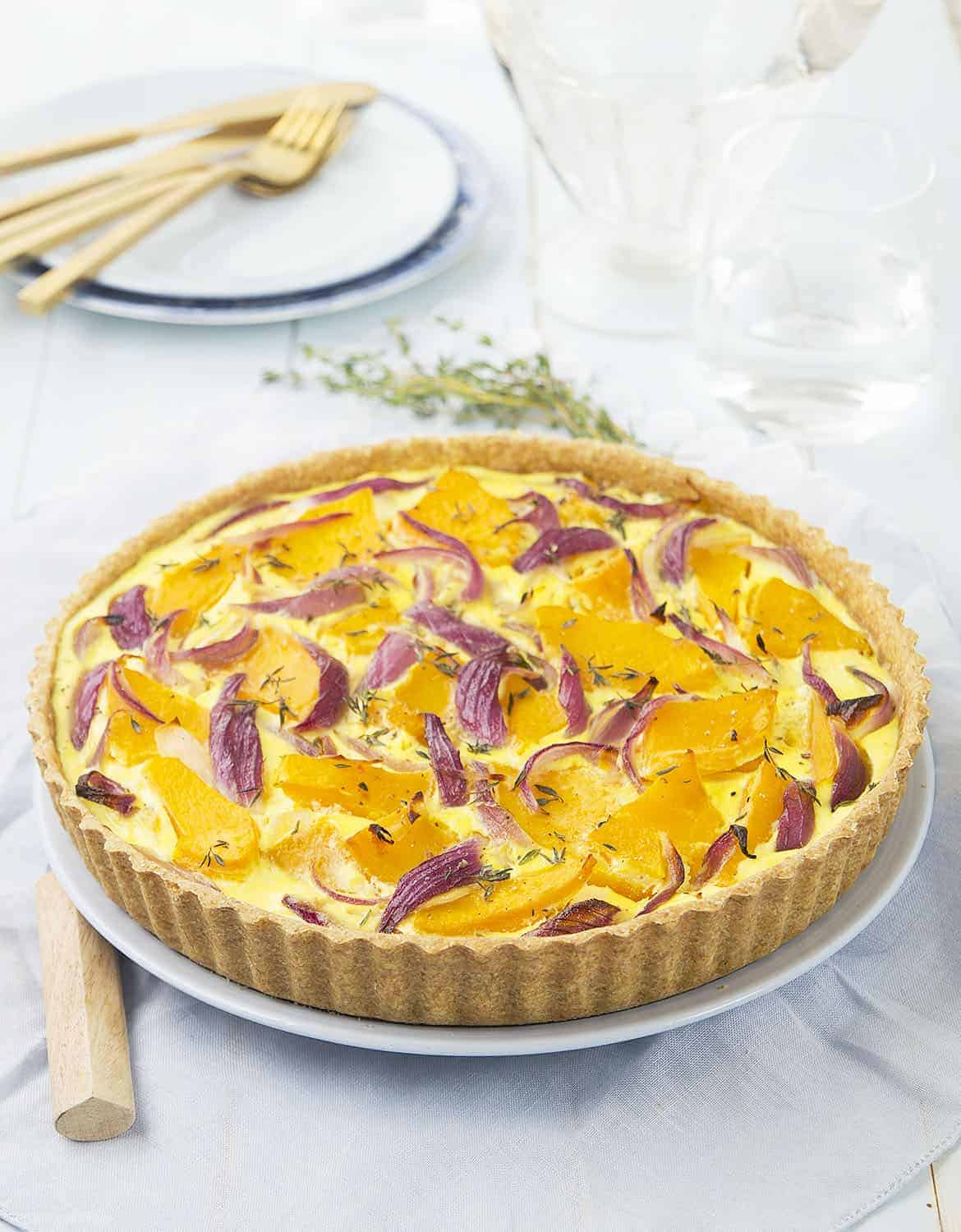 Pumpkin quiche with slices of red onion on a light blue background.