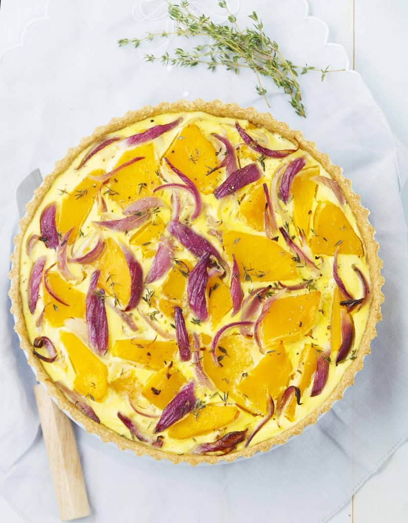 Top view of a round pumpkin quiche with slices of red onions.