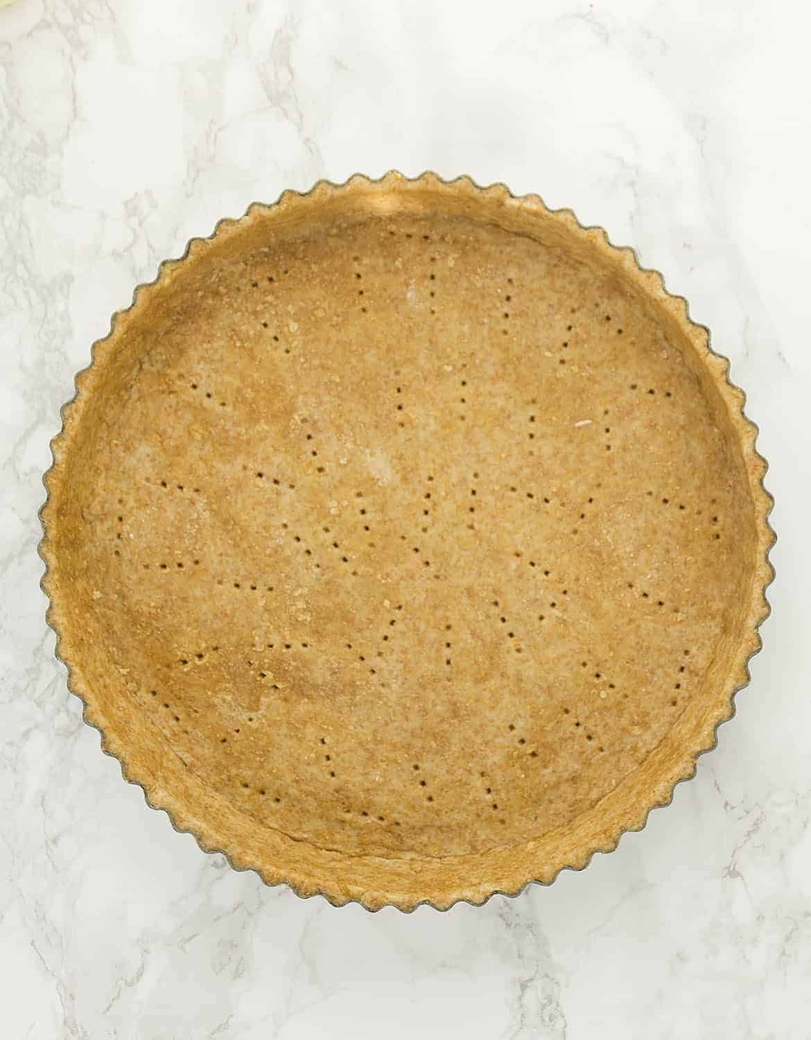 A top view of a round pie crust over a white background.