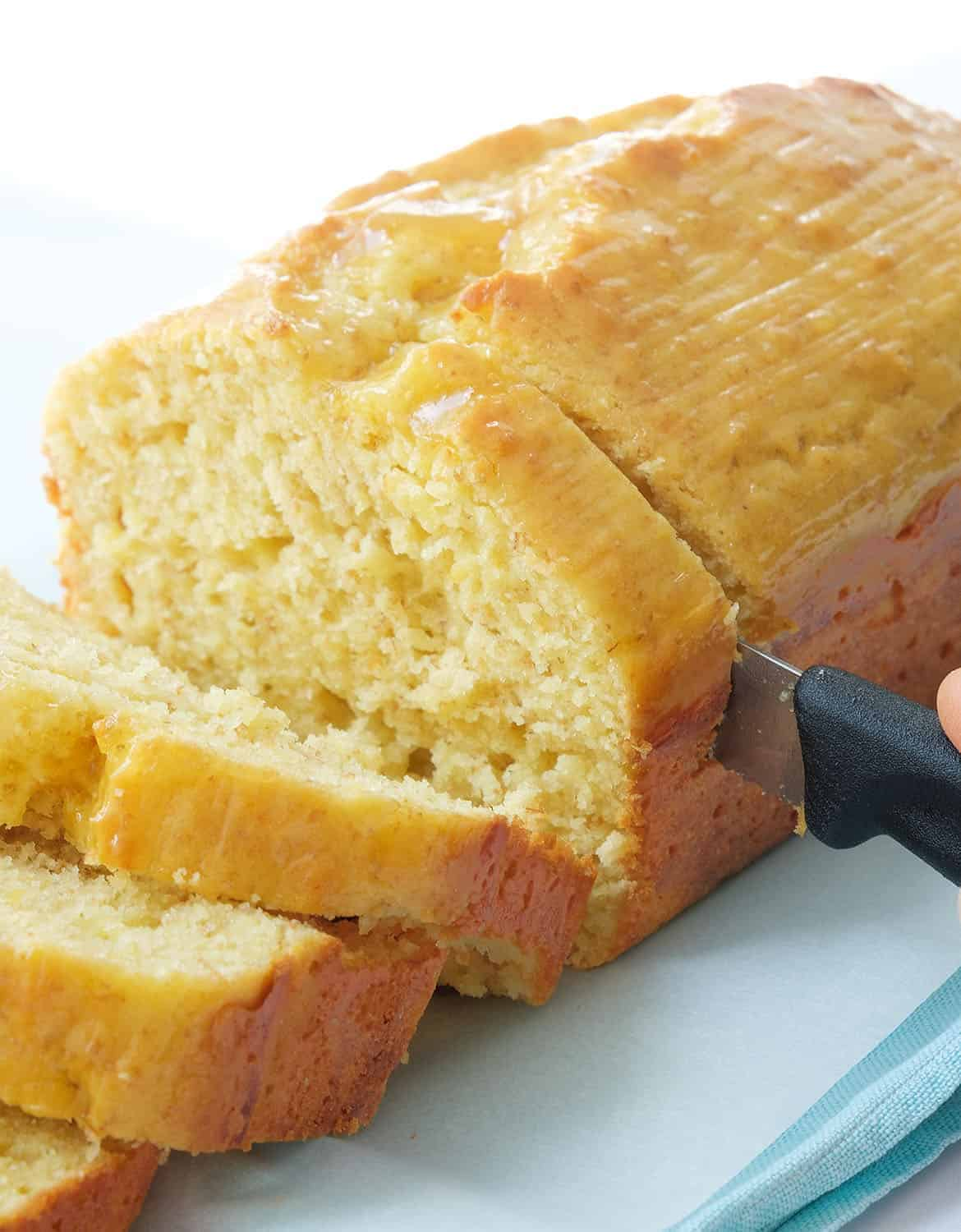 A knife cutting a healthy yogurt cake into slices over a white background.
