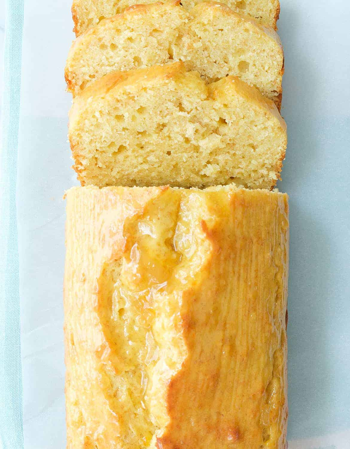 A yogurt loaf cake is cut into a few slices over a light blue background.