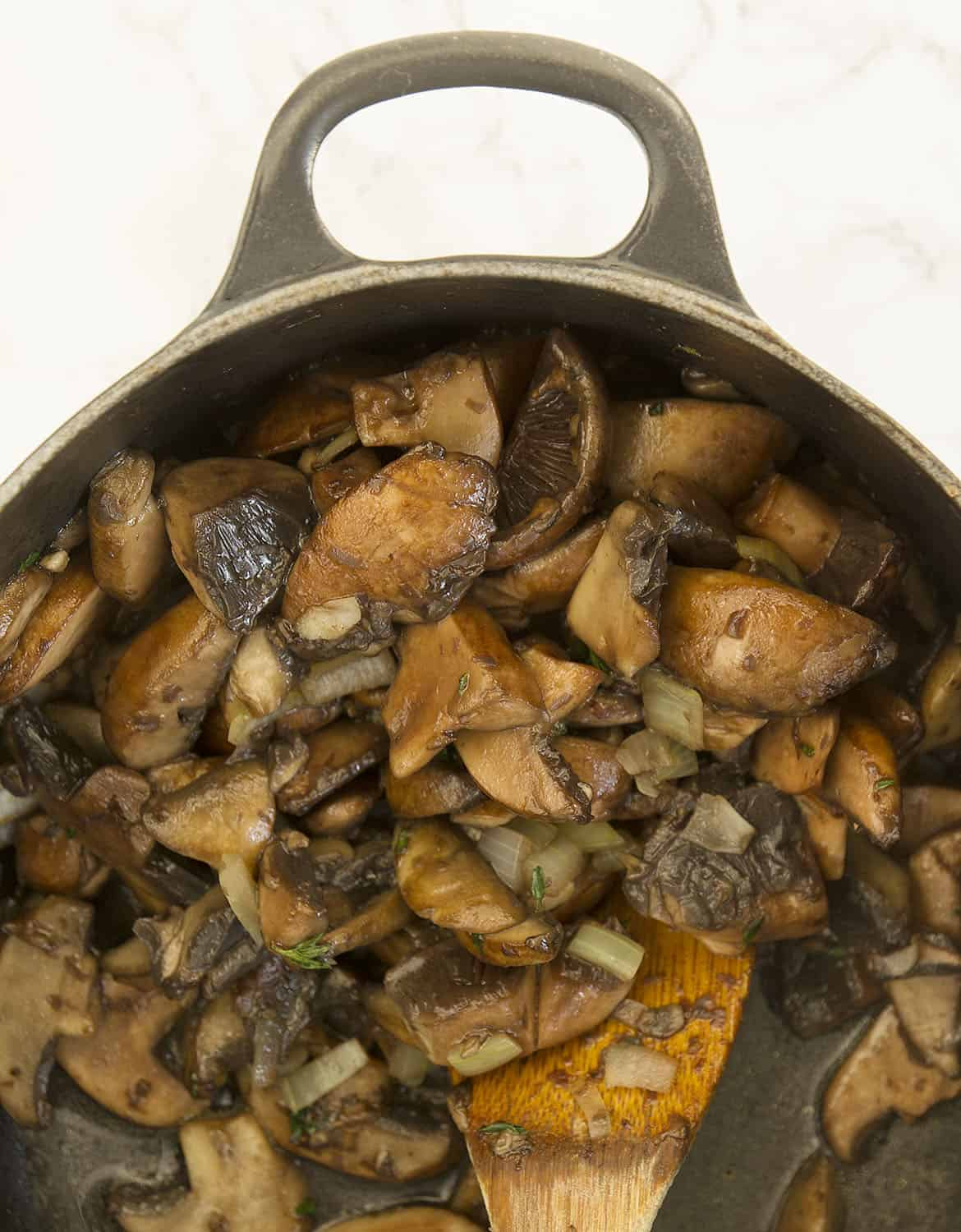 A wooden spoon stirring mushroom in a black cast iron casserole.