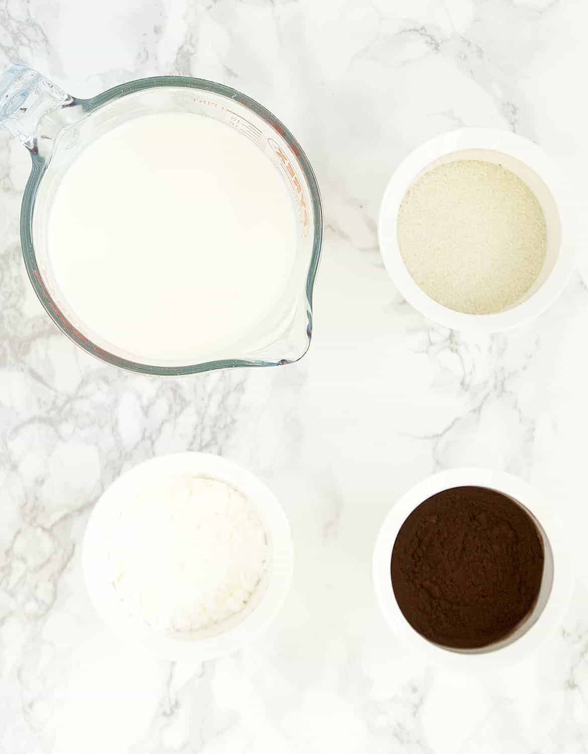 The ingredients for this easy chocolate pudding are arranges on a white marble table.