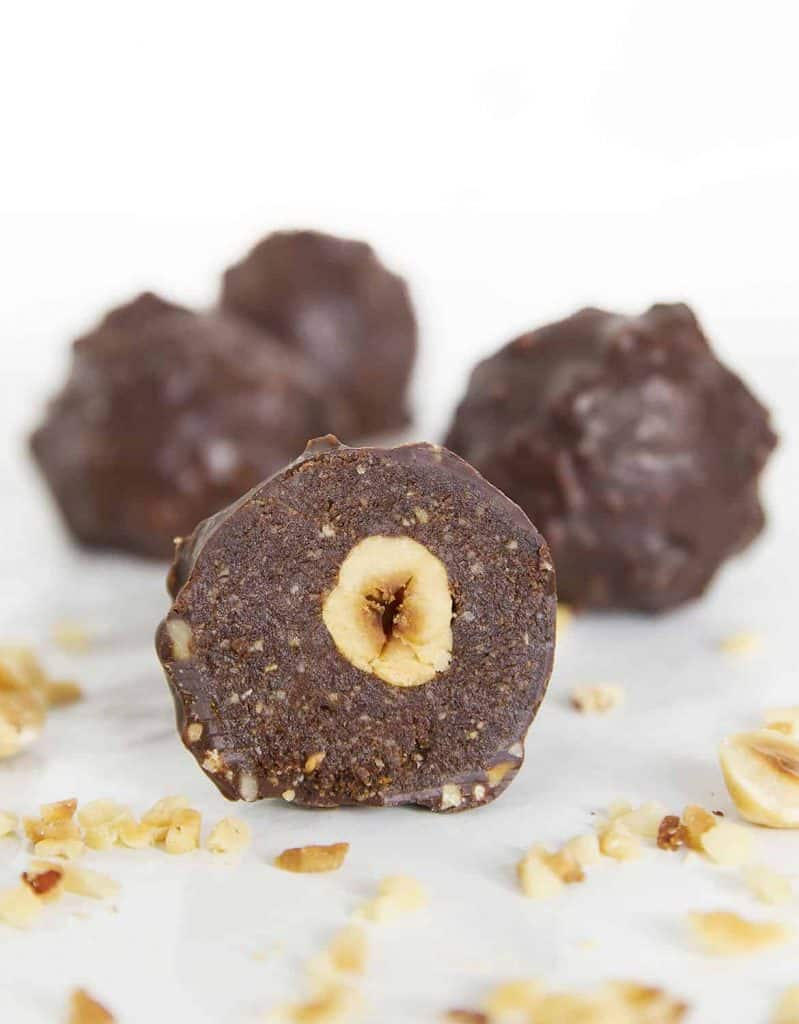 Four Homemade Ferrero Rocher truffles and chopped hazelnuts on a white background.