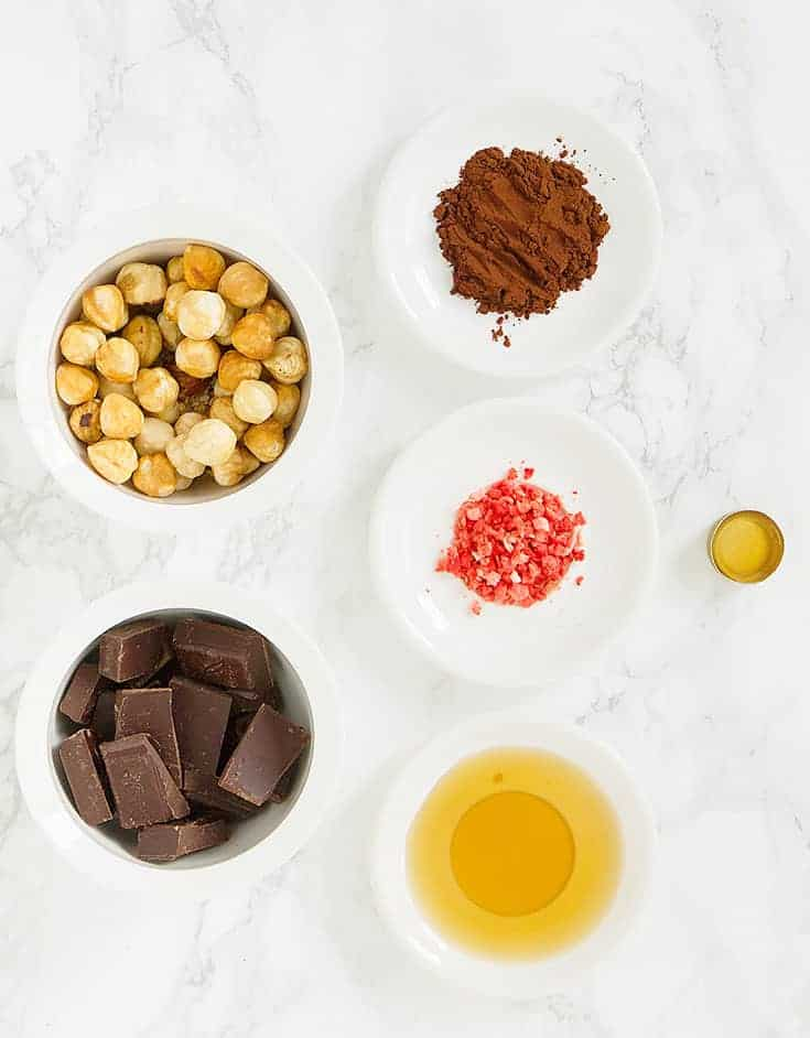 The ingredients for these vegan dark chocolate truffles with hazelnuts are arranged over a white background.