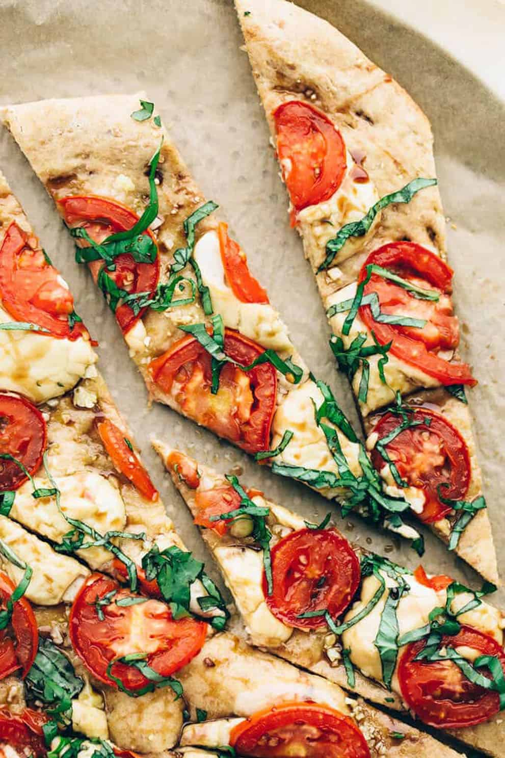 Slices of vegan caprese pizza on parchment paper - Blissful Basil