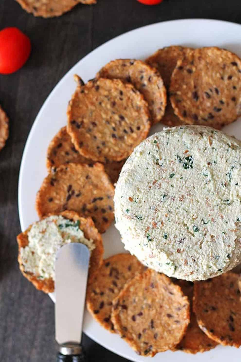 Vegan almond cheese spreadwith round crackers on a white plate - Delightful Adventures
