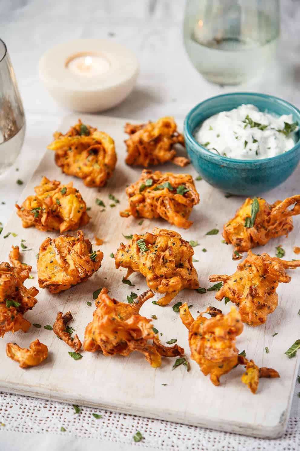 Vegan shallot bhajis with minted yogurt on a white board - UK shallots