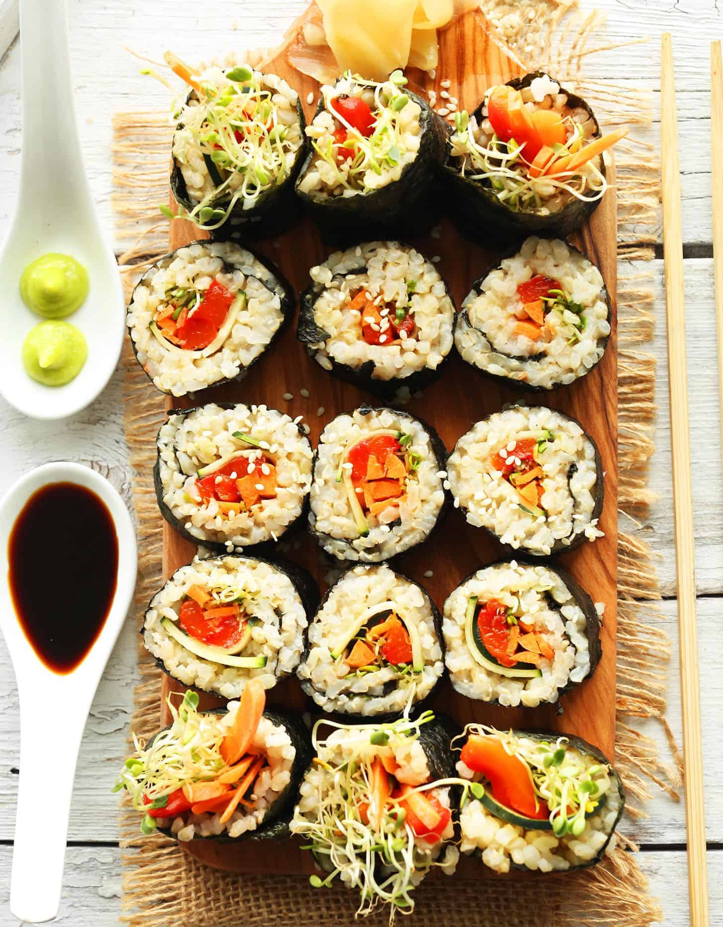 15 veggie rice sushi rolls on a rectangular wooden board - Minimalist Baker