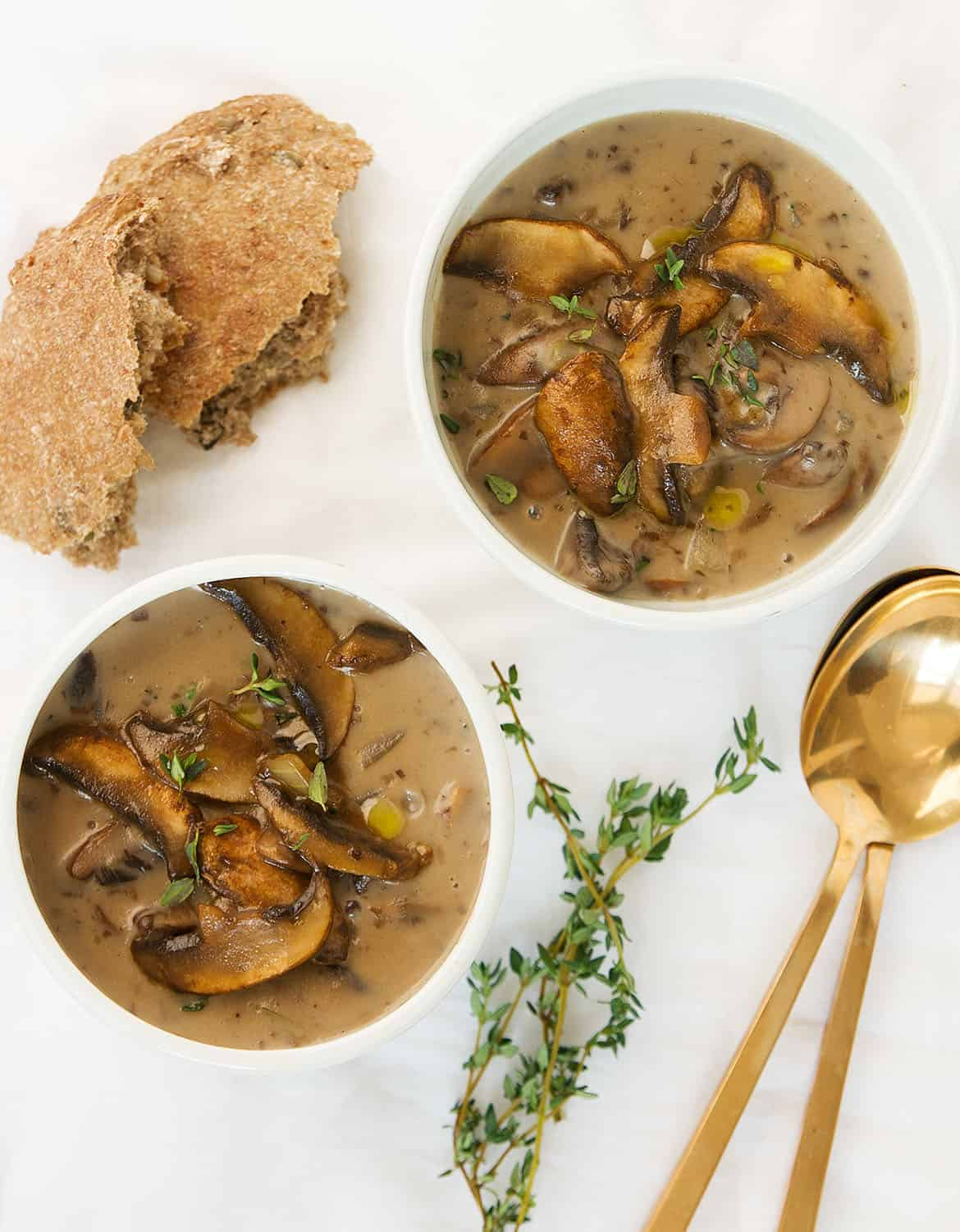 Top view of two bowls of mushroom soup over a white background.
