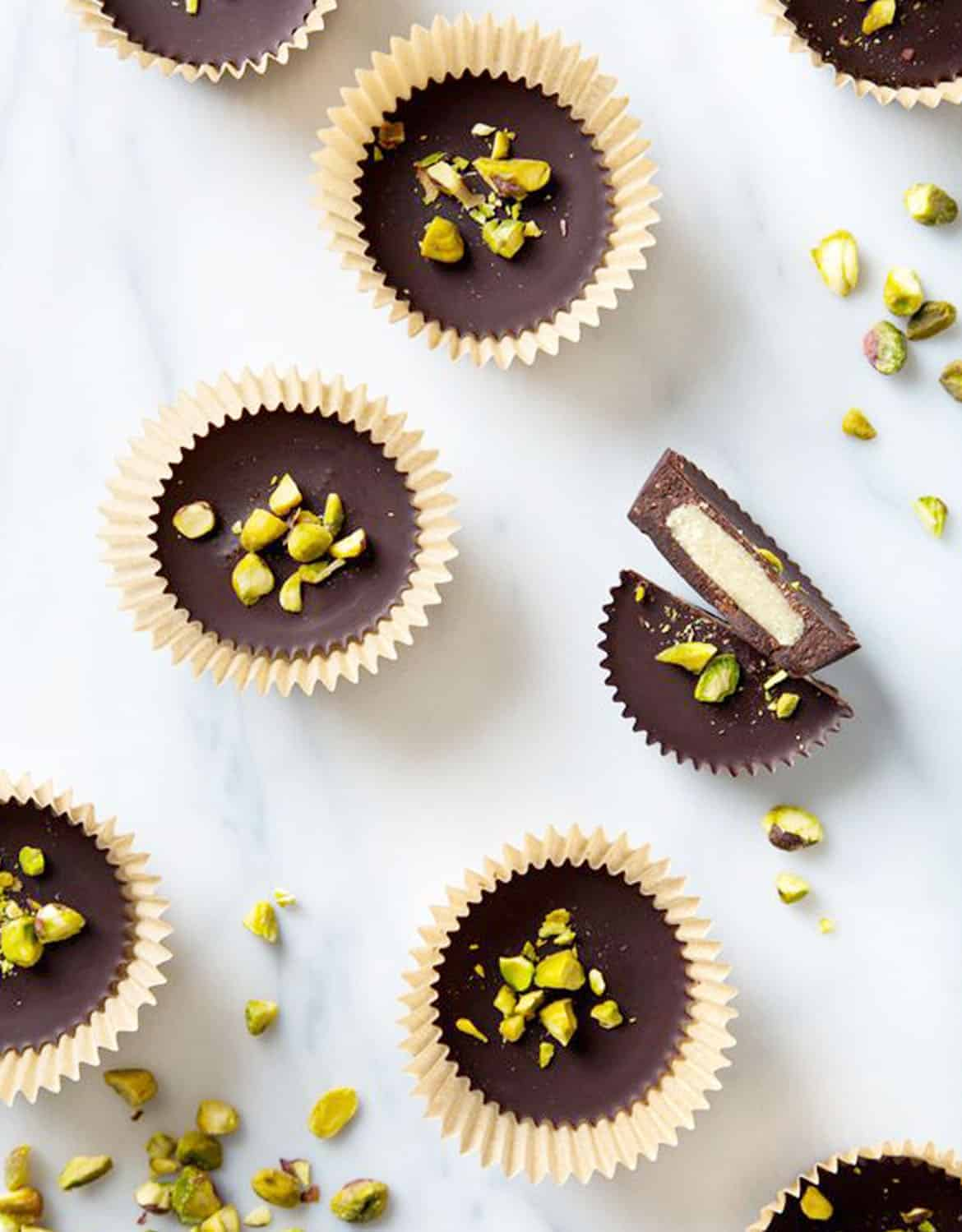 Top view of marzipan dark chocolate cups with salted pistachios over a white background - Pickles and Honey