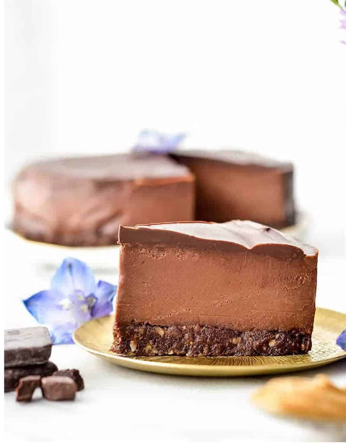 A big slice of a vegan chocolate peanut butter cheesecake, purple flowers and the whole cake in the background - Joy Food Sunshine: