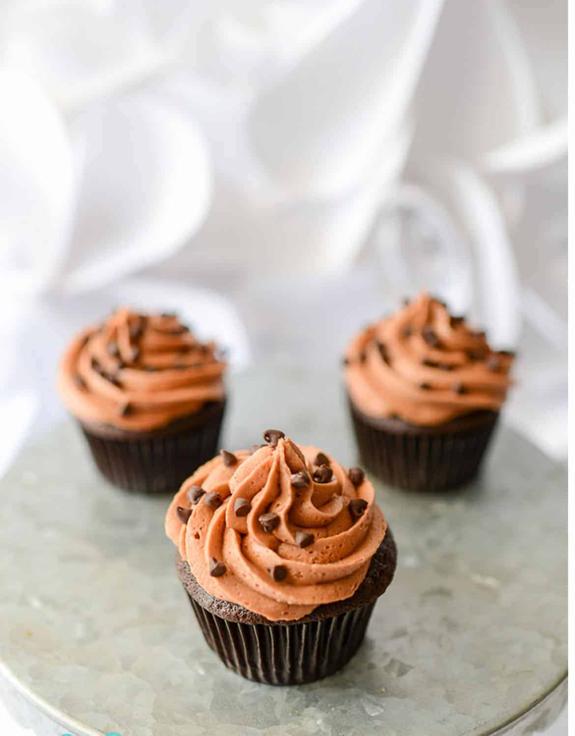 Three chocolate cupcakes decorated with frosting and chocolate chips - Tikkido