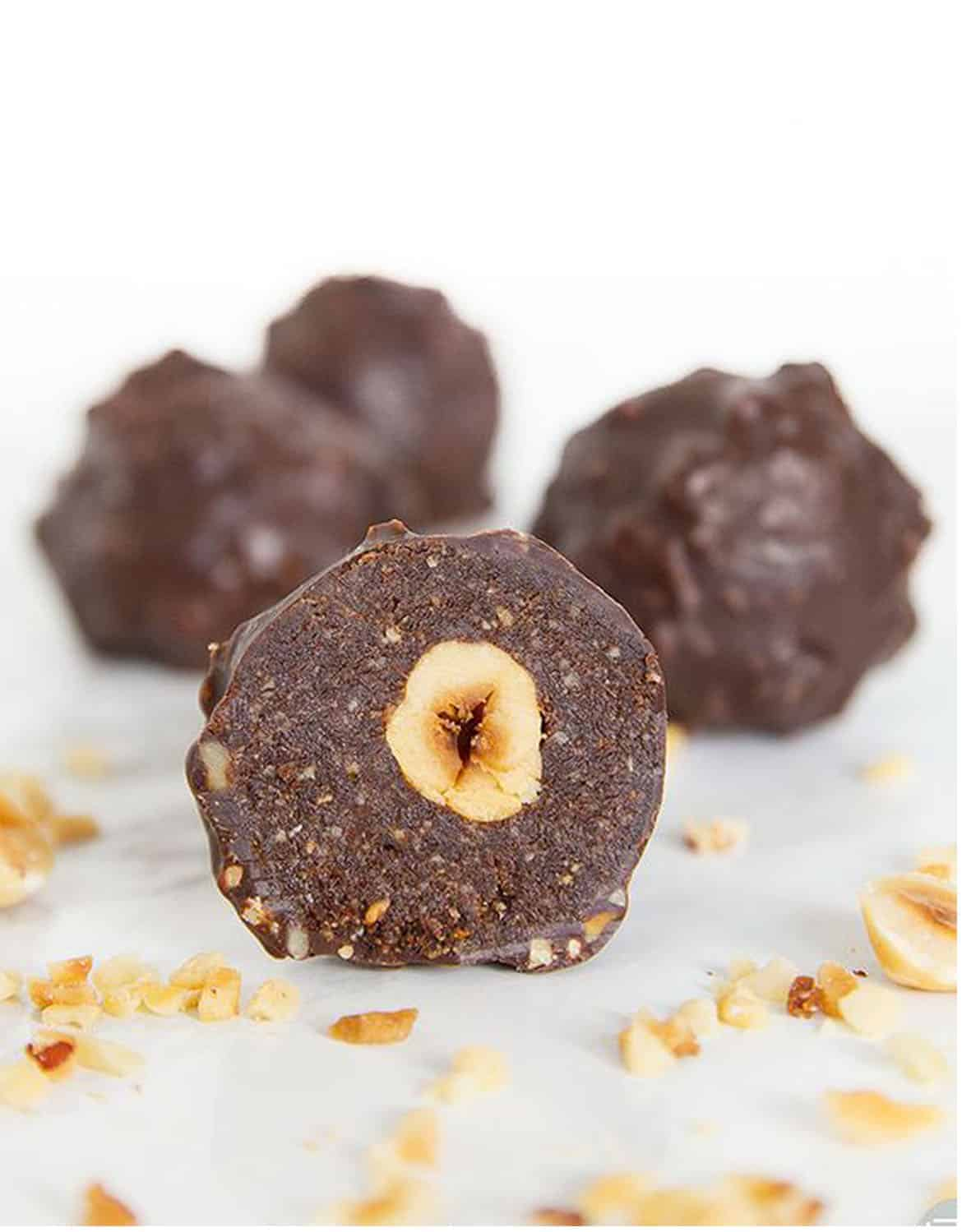 Homemade Ferrero Rocher truffles with hazelnuts over a white background - The Clever Meal