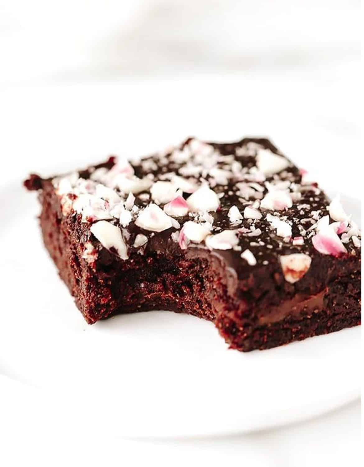 A vegan peppermint chocolate chunk brownies over a white background - Blissful Basil