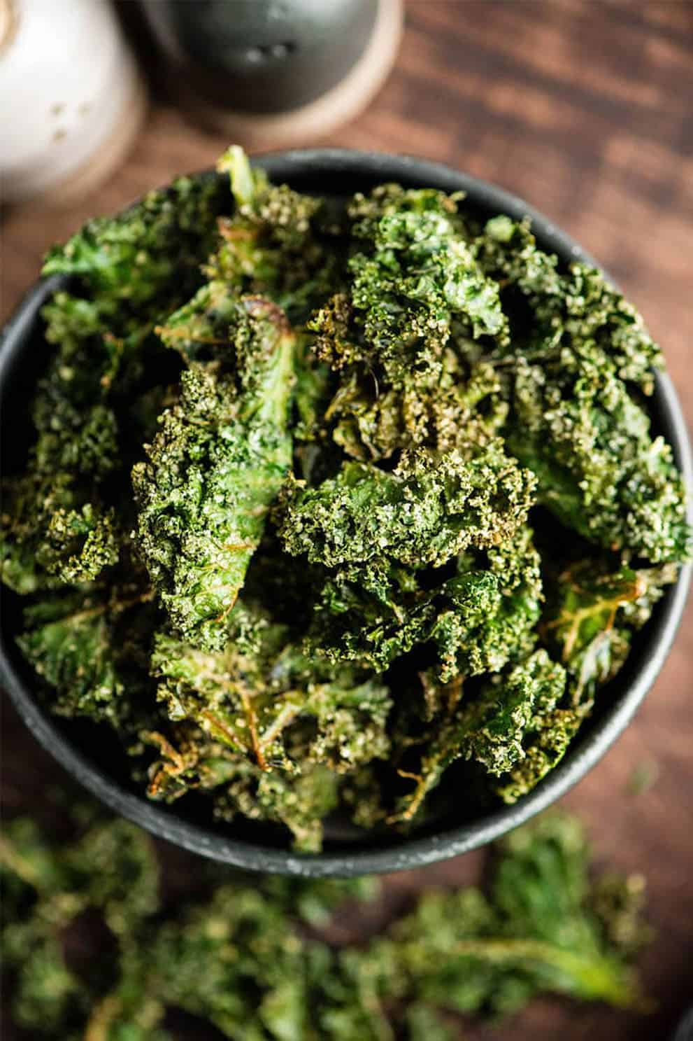 Baked kale chips in a black bowl  - Joy Food Sunshine
