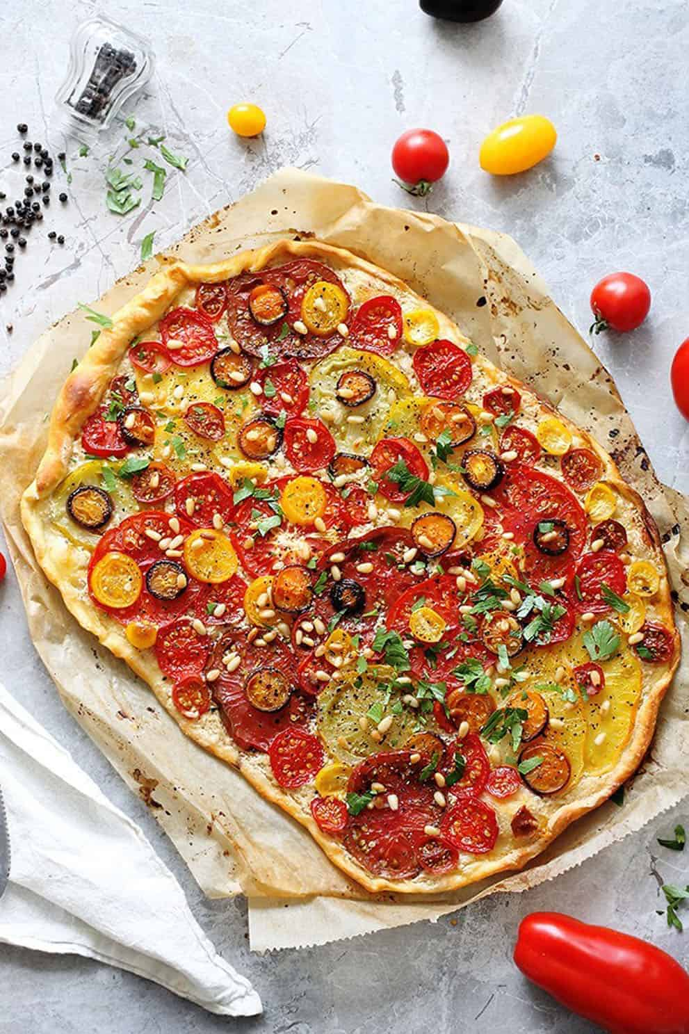 Vegan tomato flatbread on parchment paper over a grey background - Green Evi