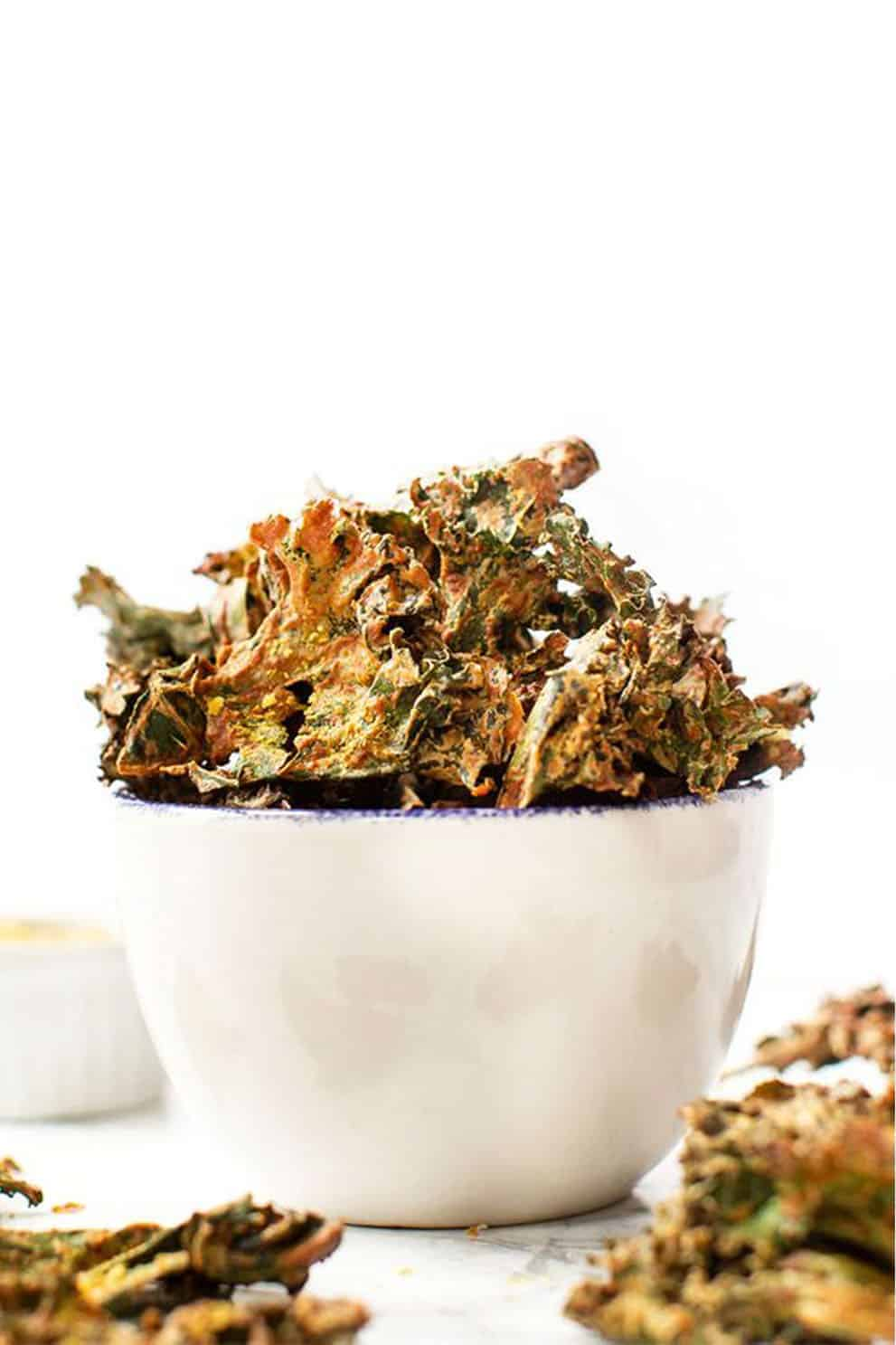 Vegan nacho kale chips in a white bowl over a white background - Simply Quinoa