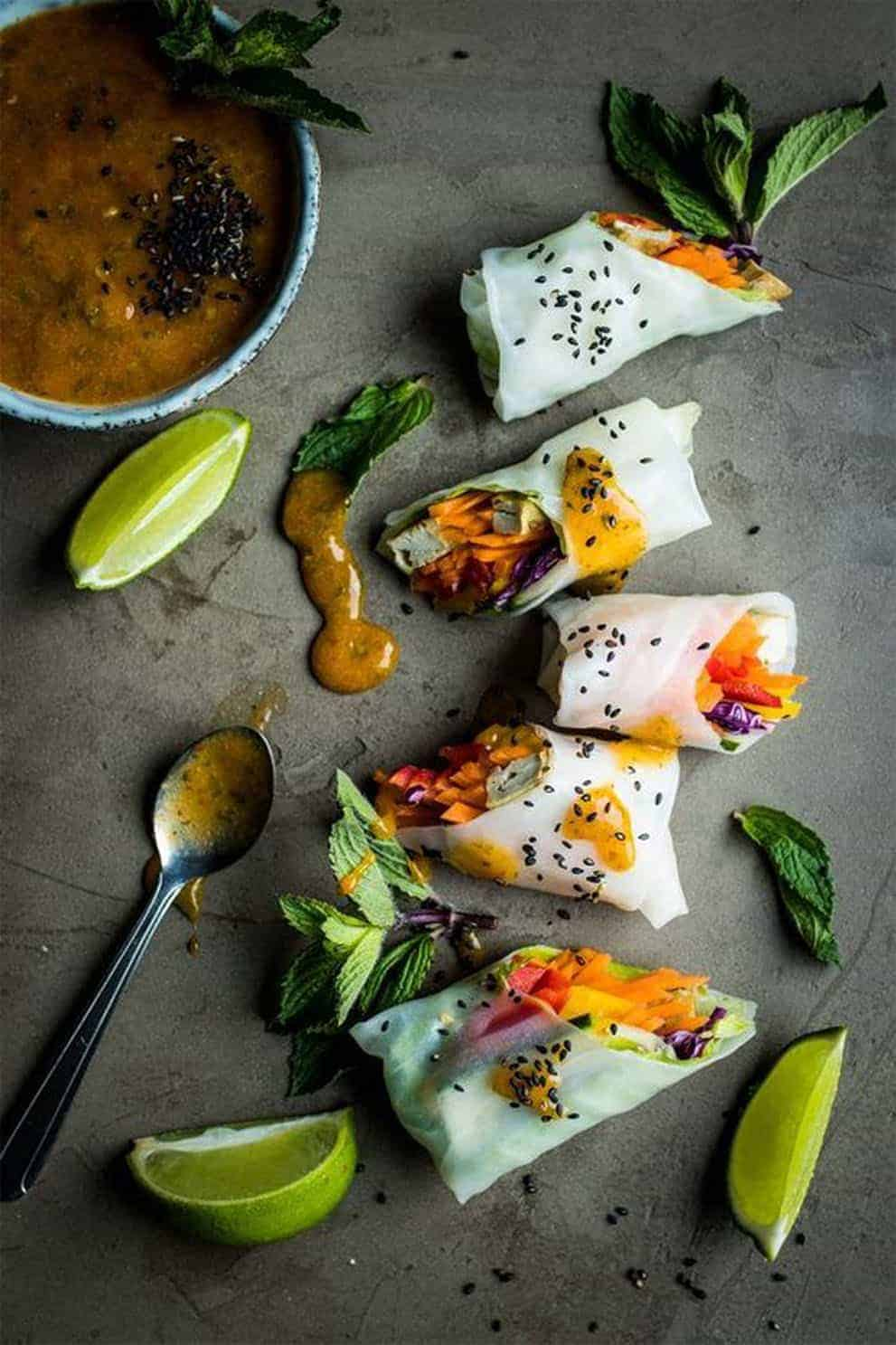 Five vegan summer rolls with dipping sauce over a grey background - Lauren Caris Cooks