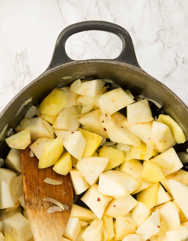 A wooden spoon stirring celeriac in a black casserole.