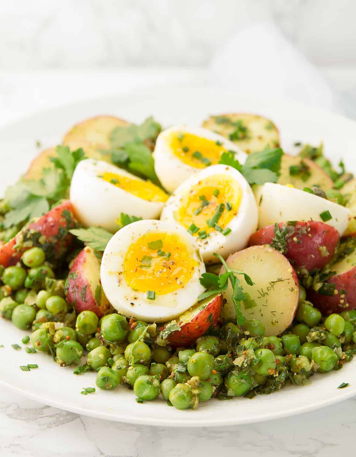 This is a delicious potato and egg salad with peas super easy to throw together, you need just a few basic and inexpensive ingredients like potatoes, eggs, frozen peas and fresh herbs. And not only is it perfect for a picnic, but it makes a nice and healthy lunch all year round.