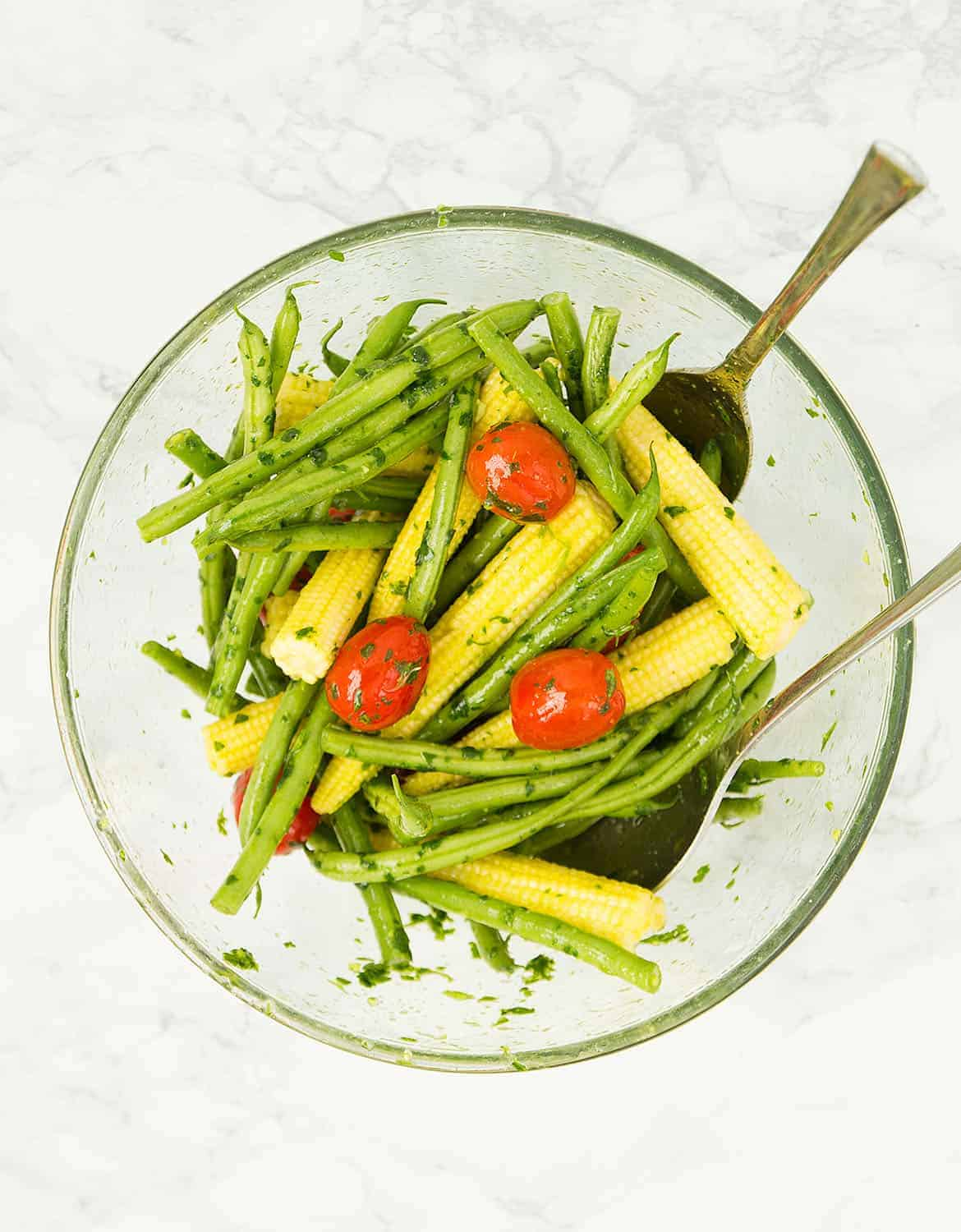 A glass bowl full of green beans, baby corns and cherry tomatoes.