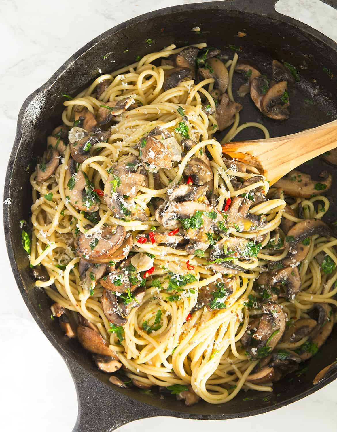 A wooden spoon is stirring the garlic mushroom pasta in a cast iron skillet.