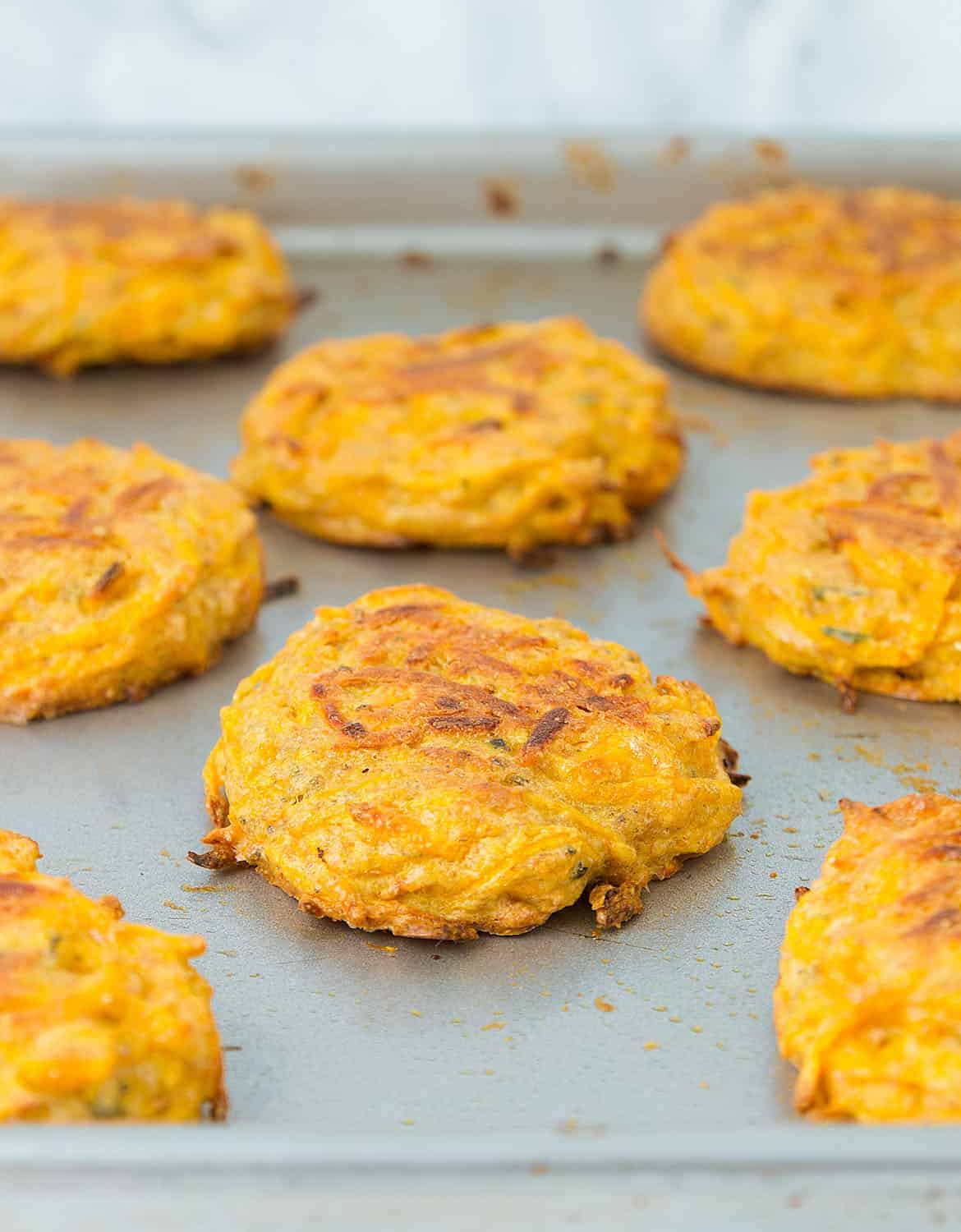 Close-up of a few butternut squash fritters on a baking pan.