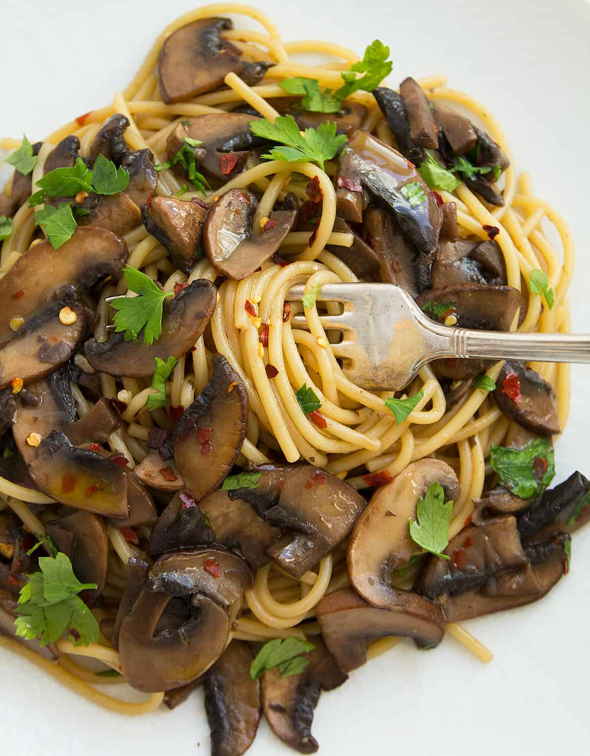 Vegan mushroom spaghetti on a white plate with a fork - The Clever Meal