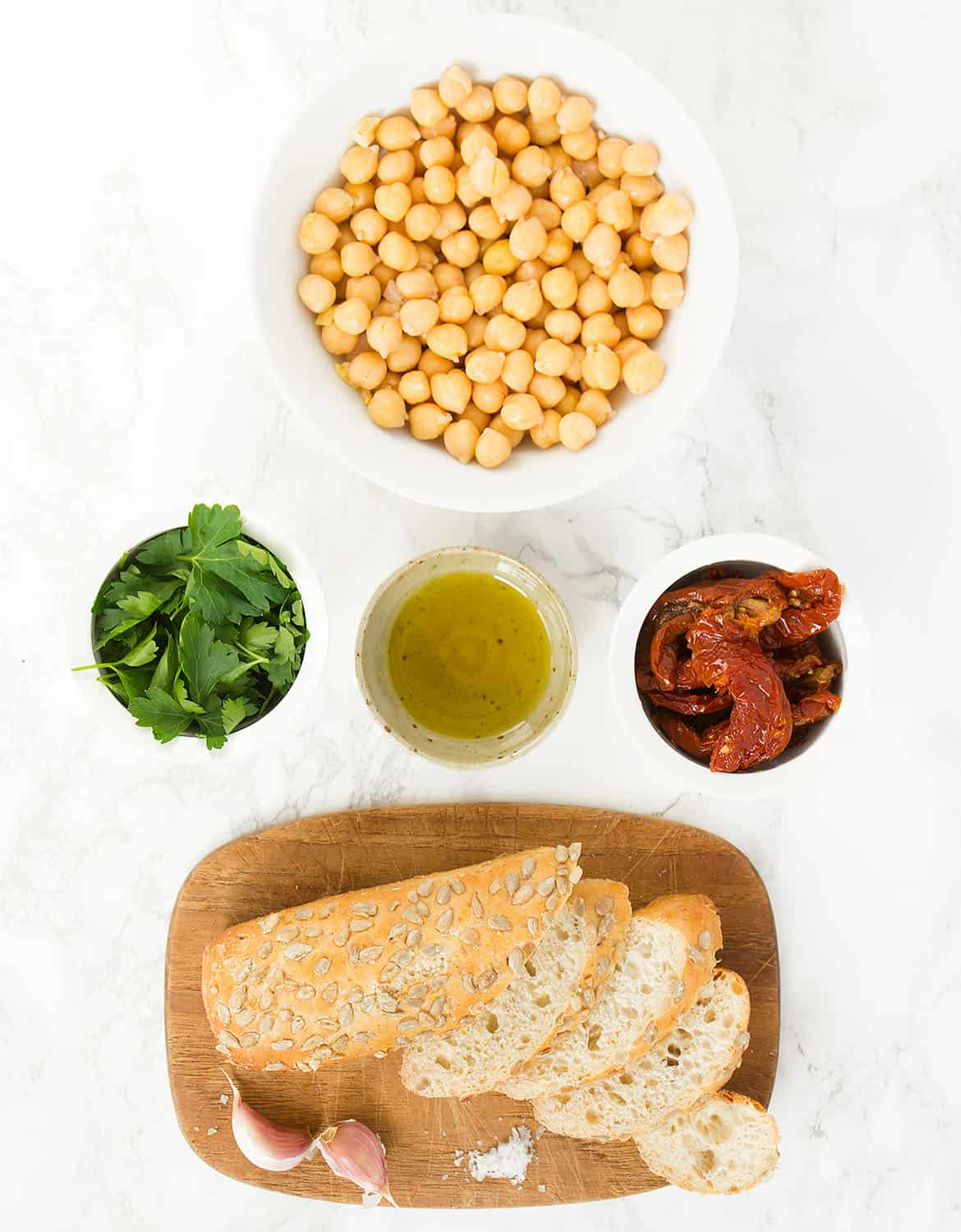 The ingredients for this chickpea bruschetta are arranged over a white background.