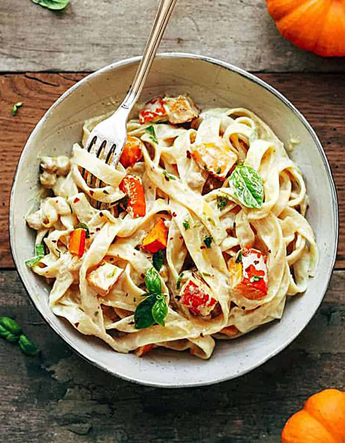 Pumpkin and chickpea pasta on light grey bowl with a fork - Full of Plants