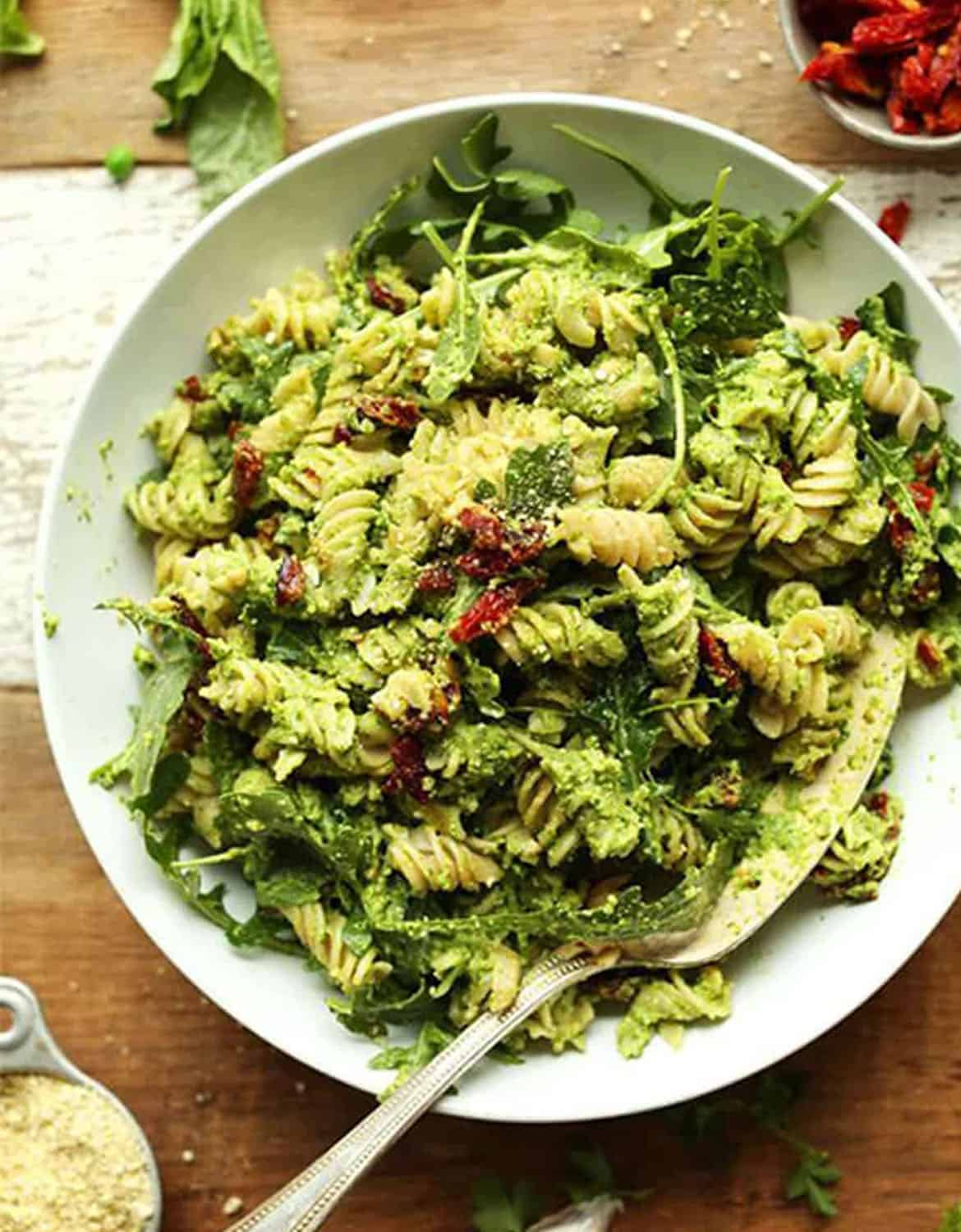 Pea pesto pasta in a white bowl with a fork - Minimalist Baker