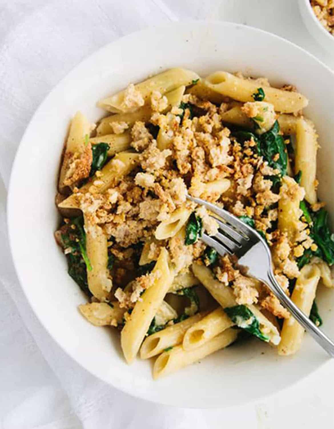 Penne with spinach and breadcrumbs in a white plate with a fork - Wall Flower Kitchen