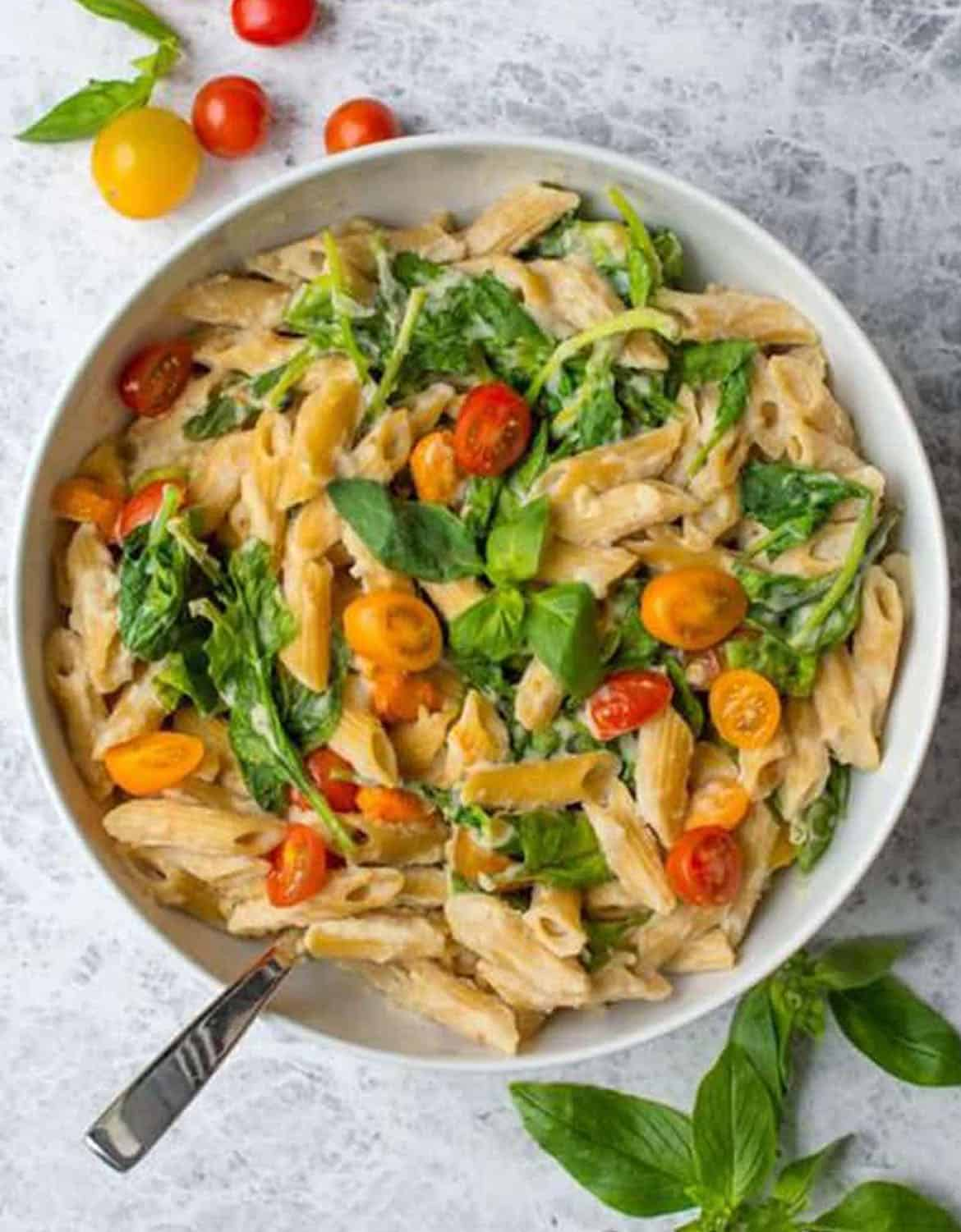 Penne with spinach, cherry tomatoes and creamy sauce in a large white bowl - Lauren Caris Cooks