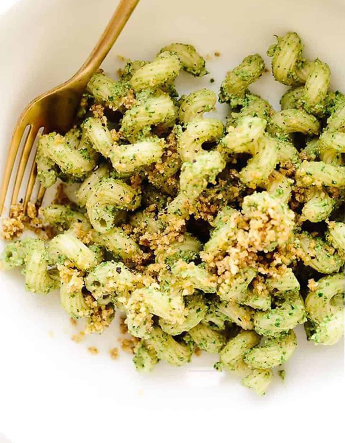 Vegan walnut pesto cavatappi on a white bowl with a golden fork - Blissful Basil