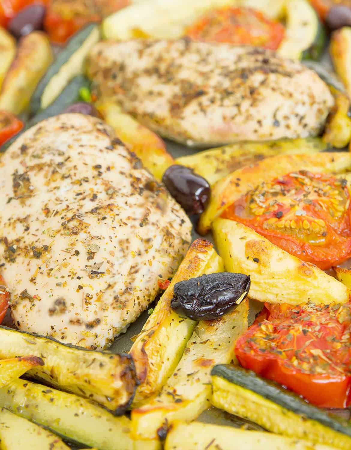 Close-up of Italian herb chicken, potatoes, tomatoes and black olives.